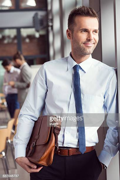 Confident businessman in the office, holding a briefcase