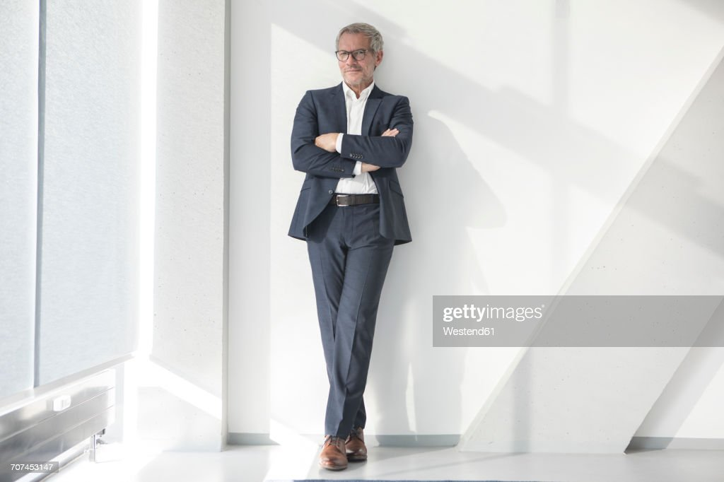 Confident businessman leaning against a wall : Stock Photo