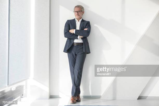 confident businessman leaning against a wall - businesswear stock pictures, royalty-free photos & images