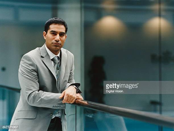 confident businessman leaning on a railing - abbigliamento da lavoro formale foto e immagini stock