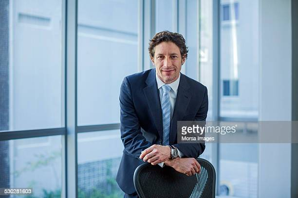 Confident businessman leaning on chair
