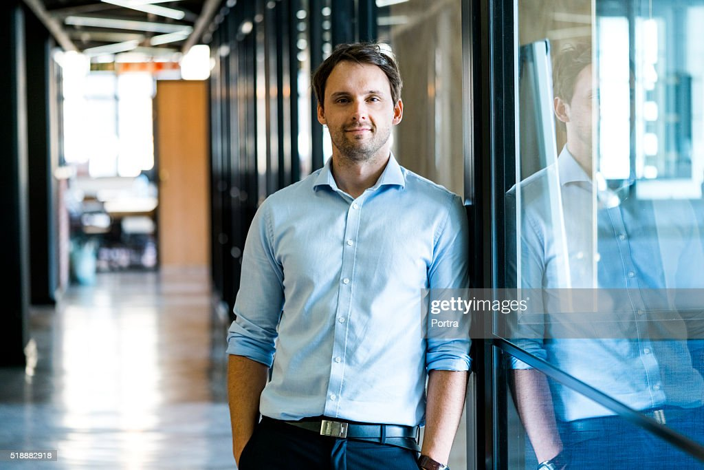 Confident businessman leaning on glass wall in office : Stock Photo