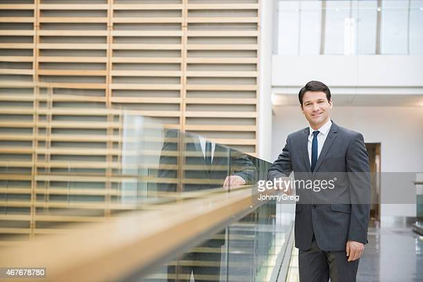 Confident Businessman Leaning On Railing In Office