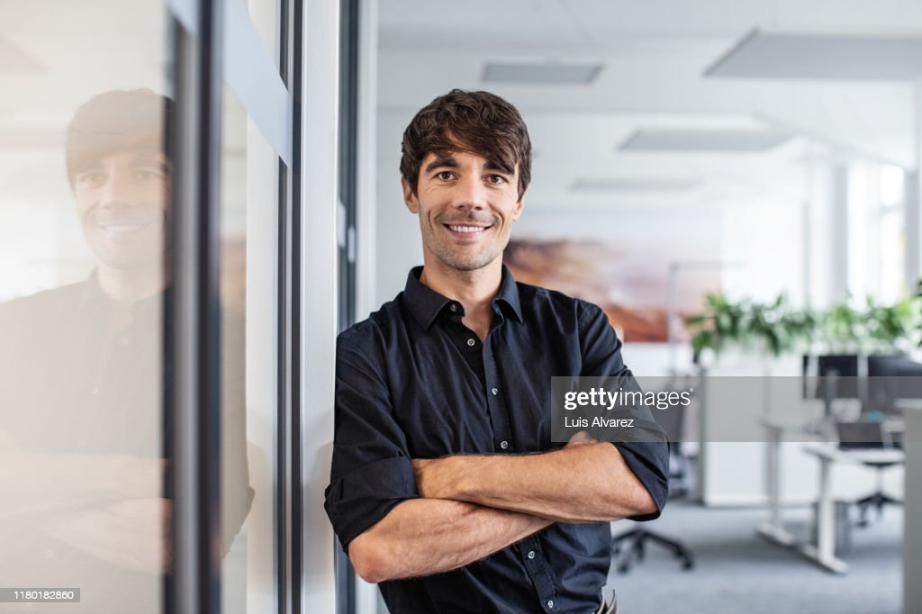 Confident businessman leaning on wall in creative office : Photo