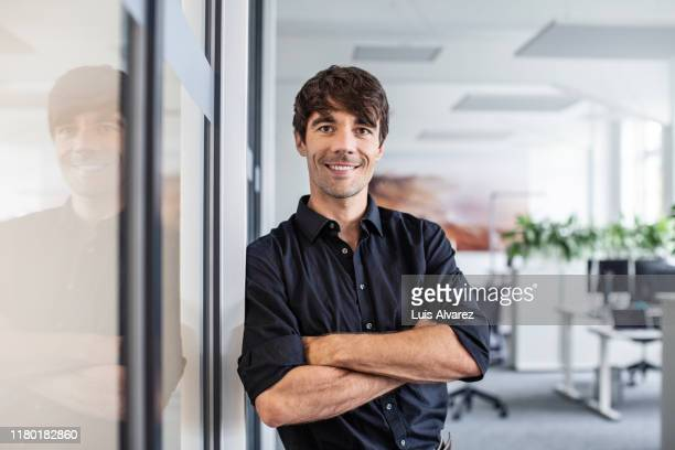 confident businessman leaning on wall in creative office - arme verschränkt stock-fotos und bilder