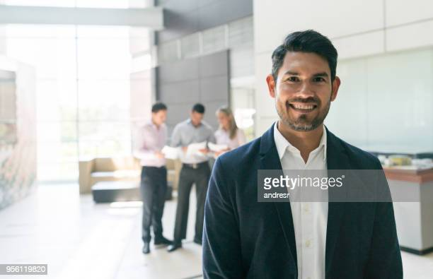 confident businessman looking at camera very happy while other business people work at the background - incidental people stock pictures, royalty-free photos & images