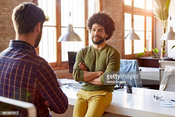 Confident businessman looking at colleague