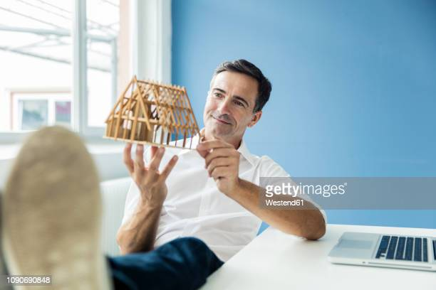 confident businessman looking at model house in office - investition stock-fotos und bilder