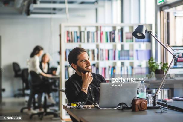confident businessman looking away while sitting at desk in office - incidental people stock pictures, royalty-free photos & images