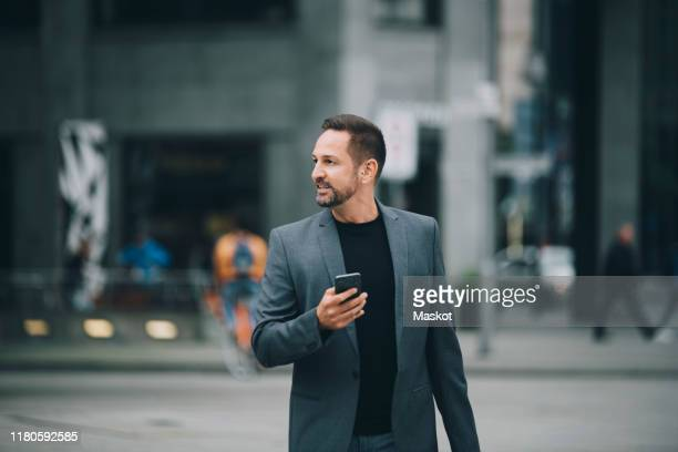 confident businessman looking away while walking on street in city - incidental people stock pictures, royalty-free photos & images