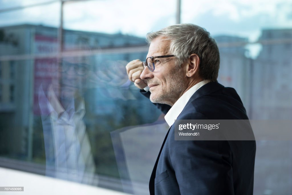 Confident businessman looking out of window : Stock-Foto