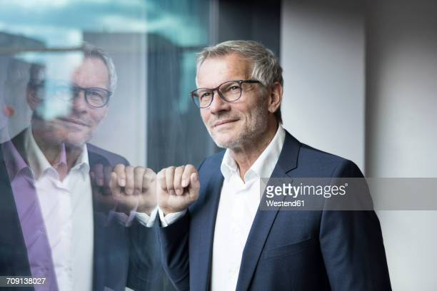 confident businessman looking out of window - spiegelung stock-fotos und bilder