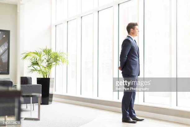 Confident businessman looking through office window