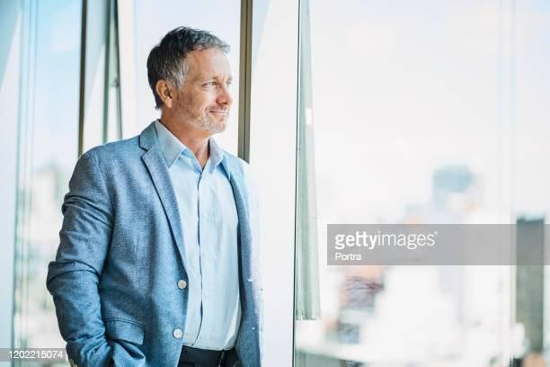 zekere zakenman die door venster kijkt - businessman stockfoto's en -beelden