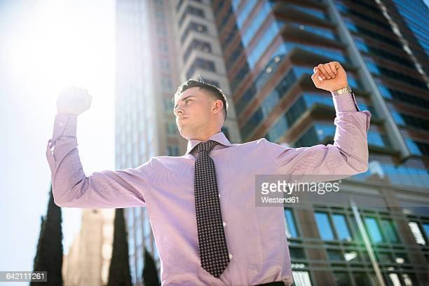 Confident businessman outdoors raising his arms