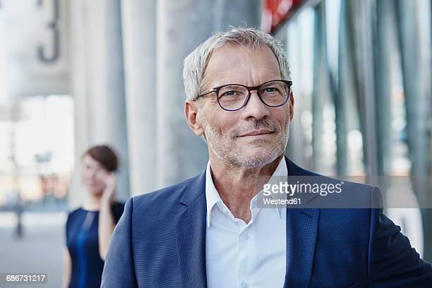 confident businessman outdoors with woman in background - 55 59 años fotografías e imágenes de stock