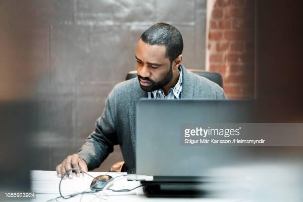 Confident businessman reading document at desk