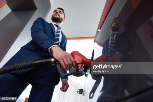 confident businessman refueling car at gas station - gas tank stock photos and pictures