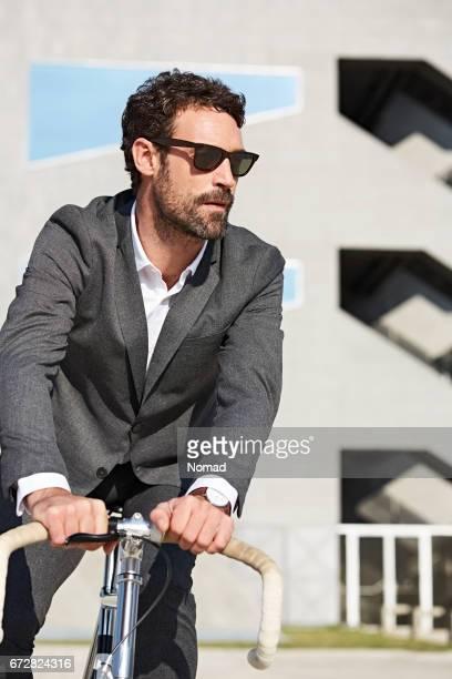 bicicleta de equitação empresário confiante na cidade - adulto de idade mediana - fotografias e filmes do acervo
