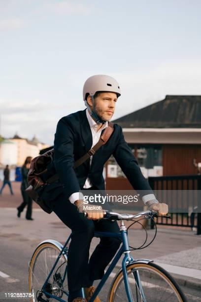 confident businessman riding bicycle on street in city - blazer vert photos et images de collection