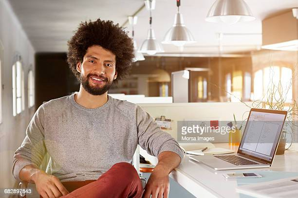 confident businessman sitting at desk - sweatshirt stock pictures, royalty-free photos & images