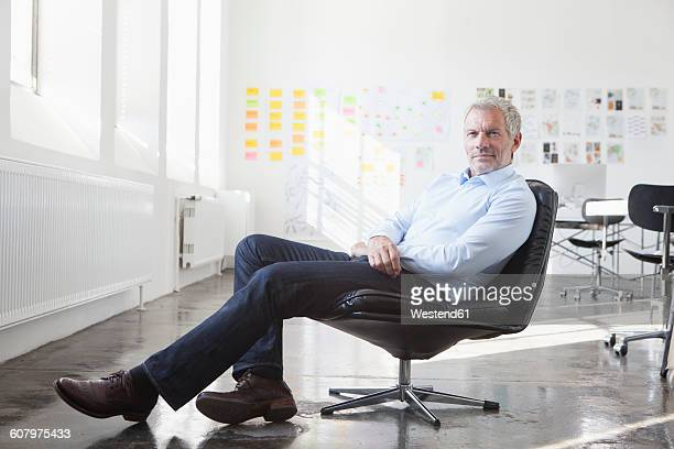 Confident businessman sitting in chair in office