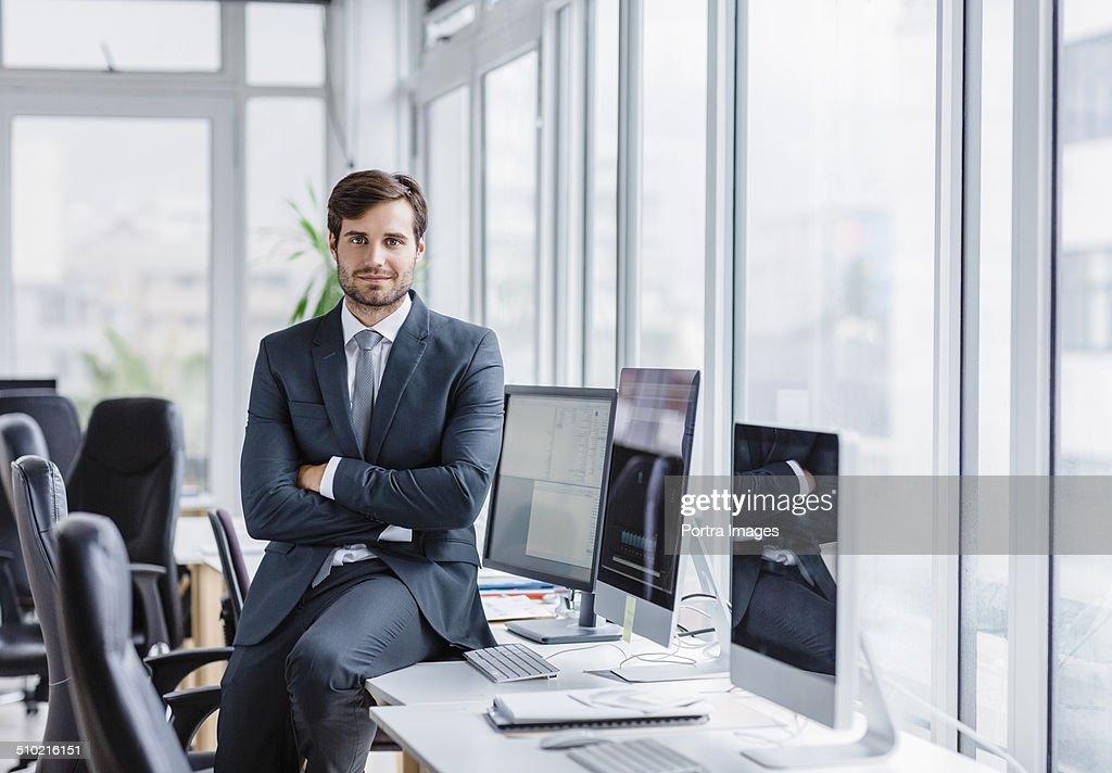 Confident businessman sitting on computer desk : ストックフォト