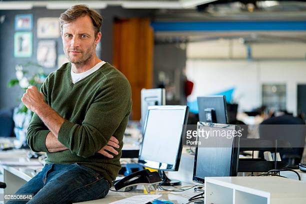 Confident businessman sitting on computer table
