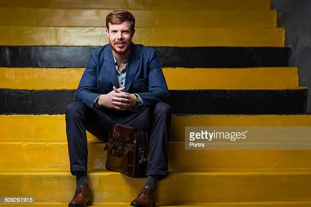 Confident businessman sitting on yellow steps