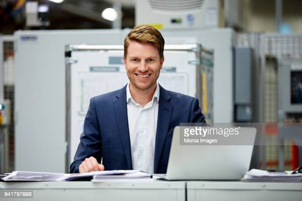 Confident businessman sitting with laptop at desk