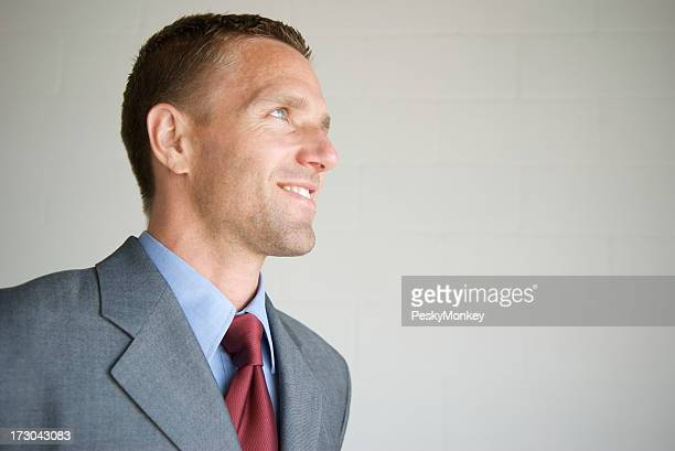 Confident Businessman Smiles in Profile