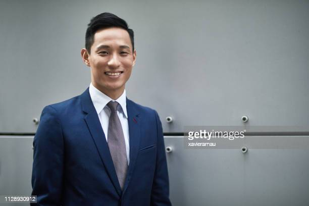 confident businessman smiling against wall - blue suit stock pictures, royalty-free photos & images