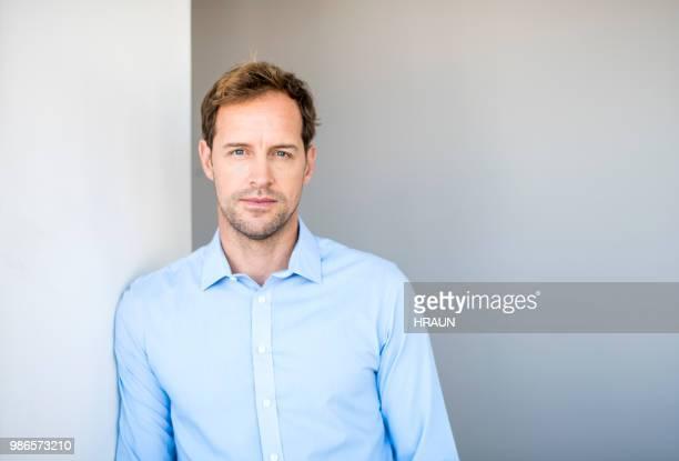 confident businessman standing against wall - camisa com botões imagens e fotografias de stock