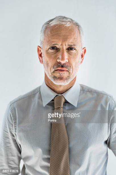 Confident businessman standing against white wall