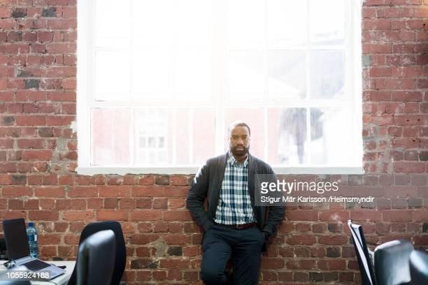 Confident businessman standing against window