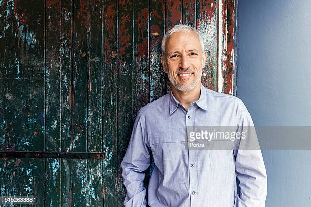 confident businessman standing against wooden wall - 40 49 jaar stockfoto's en -beelden