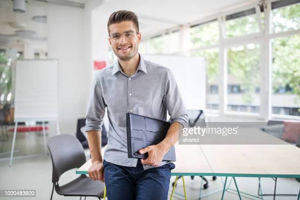 confident businessman standing by conference table - lavoratori dipendenti foto e immagini stock