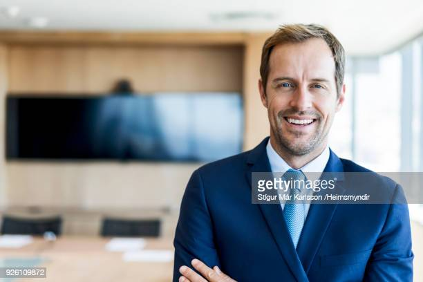 Confident businessman standing in board room