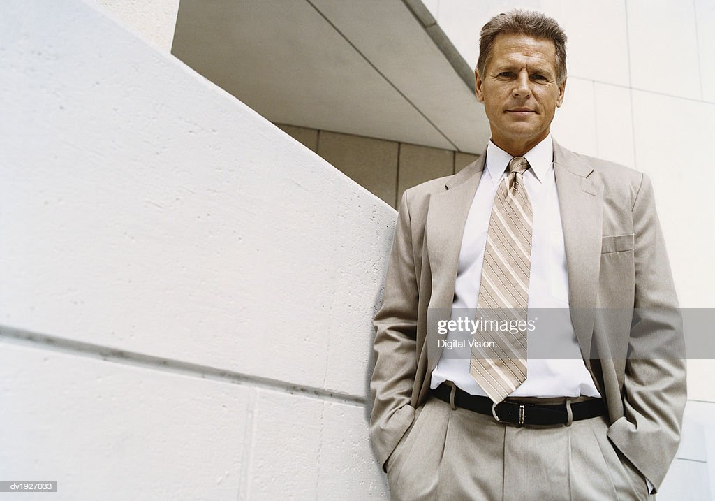 Confident Businessman Standing in Front of a Building Exterior : Stock Photo