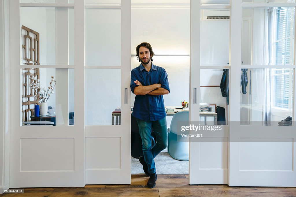 Confident businessman standing in office : Stock Photo