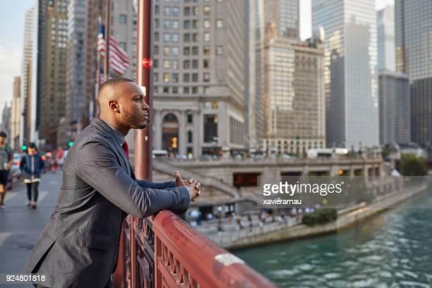 Confident businessman standing on bridge in city