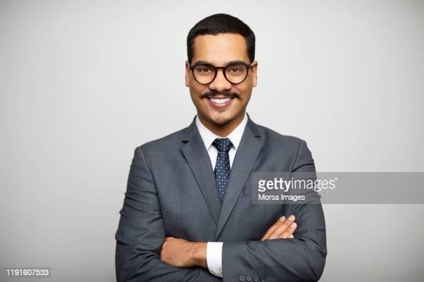 confident businessman standing with arms crossed - formal portrait - fotografias e filmes do acervo