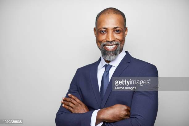 confident businessman standing with arms crossed - headshot stock pictures, royalty-free photos & images