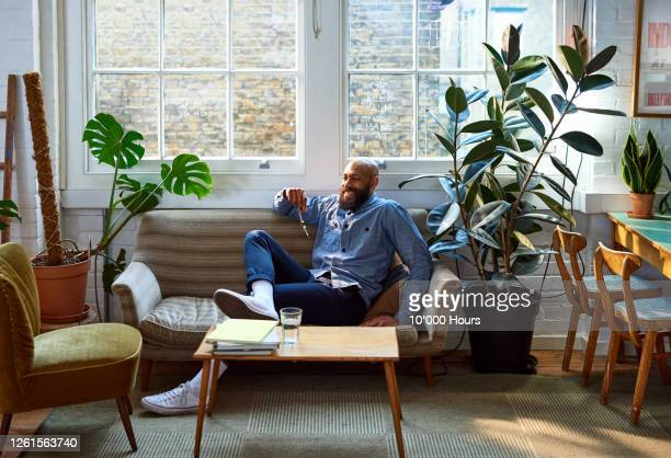 confident businessman taking break in office - sofa stock pictures, royalty-free photos & images