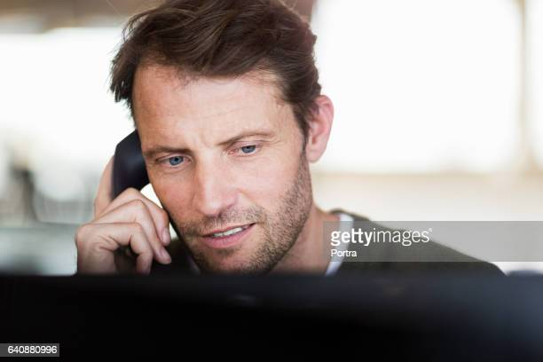 Confident businessman talking on phone at office