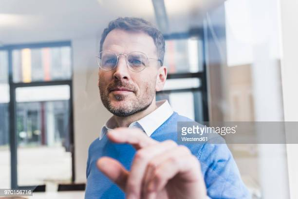 confident businessman touching glass pane - konzentration stock-fotos und bilder