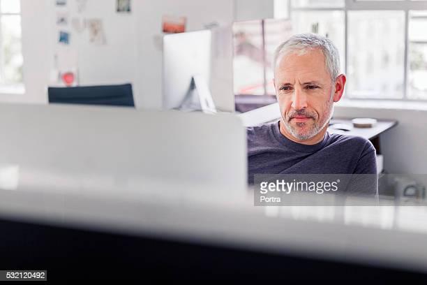 Zuversichtlich Geschäftsmann mit desktop-PC im Büro