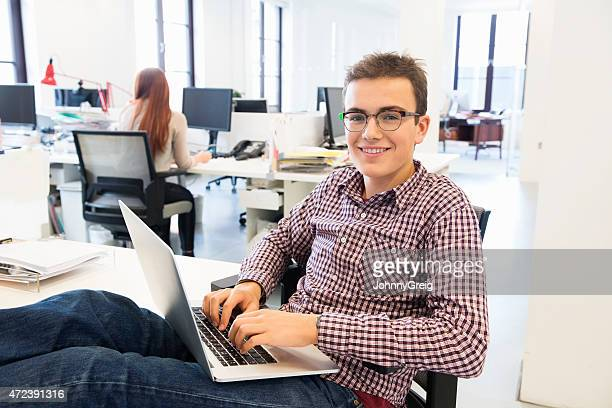 confident businessman using laptop with feet up on table - 18 19 years stock pictures, royalty-free photos & images