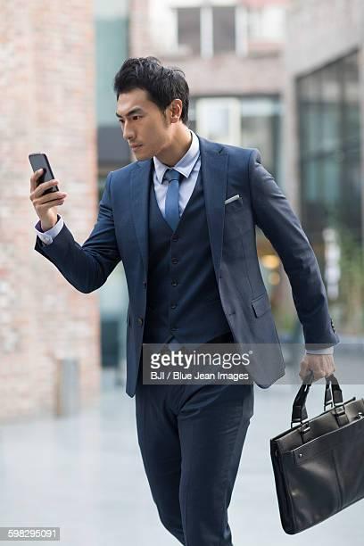Confident businessman using smart phone