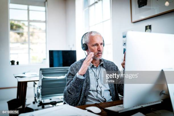 confident businessman video conferencing at desk - video conference stock pictures, royalty-free photos & images